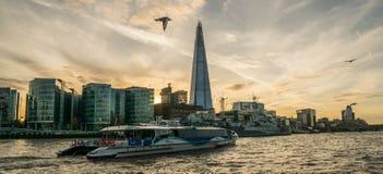 LONDON UK - Oktober 17th, 2017: Skärvabyggnadssikten från Themsenflodstranden med floden som kryssar omkring skepp i sikten, soln Fotografering för Bildbyråer