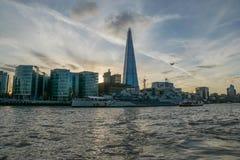 LONDON UK - Oktober 17th, 2017: Skärvabyggnadssikten från Themsenflodstranden med floden som kryssar omkring skepp i sikten, soln Arkivbilder