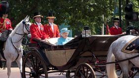 Queen Elizabeth II travels along The Mall in an open carriage pulled by horses, on her way to the Trooping of the Colour parade.
