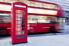 London, UK. Red telephone booth and red bus passing. Symbols of England. London, UK. Red telephone booth and red bus passing in motion blur. Symbols of Great Stock Image