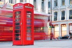 London, UK. Red telephone booth and red bus passing. Symbols of England. stock images