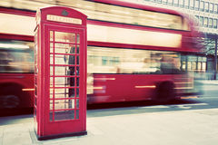 London, UK. Red telephone booth and red bus passing. Symbols of England. royalty free stock photo