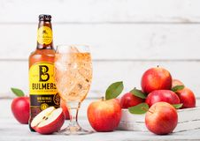 LONDON, UK - SEPTEMBER 13, 2018: Bottle of Bulmers Original Cider and glass of ice cubes with fresh apples on wooden background. Stock Images