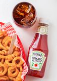 LONDON, UK - SEPTEMBER 10, 2018: Bottle of Heinz tomato ketchup on white kitchen background with glass of cola and curly fries. LONDON, UK - SEPTEMBER 10, 2018 royalty free stock photo