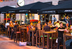 LONDON, UK - 7 SEPTEMBER, 2015: Canary Wharf night life. People sitting in local restaurant after long hours working day Stock Photos