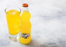 LONDON UK - SEPTEMBER 28, 2018: Exponeringsglas och flaskan av Fanta Orange sodavatten dricker med iskuber och bubblor på stenkök royaltyfri foto