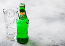 LONDON UK - SEPTEMBER 28, 2018: Exponeringsglas och flaskan av Sprite sodavatten dricker med iskuber och bubblor på stenköksbordb arkivbild