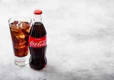 LONDON, UK - SEPTEMBER 28, 2018: Glass and bottle of Coca Cola soda drink with ice cubes and bubbles on stone kitchen table backgr stock photography