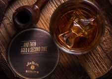 LONDON, UK - SEPTEMBER 04, 2018: Glass of Jim Beam Bourbon whiskey with original coaster and vintage smoking pipe on wood. royalty free stock images