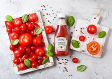 LONDON, UK - SEPTEMBER 13, 2018: Heinz ketchup with fresh raw tomatoes in box on stone kitchen background. LONDON, UK - SEPTEMBER 13, 2018: Heinz ketchup with stock image