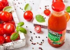 LONDON, UK - SEPTEMBER 13, 2018: Heinz tomato juice with fresh raw tomatoes in box on stone kitchen background. LONDON, UK - SEPTEMBER 13, 2018: Heinz tomato royalty free stock photo