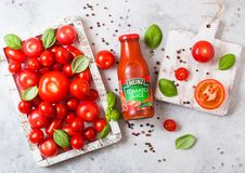 LONDON, UK - SEPTEMBER 13, 2018: Heinz tomato juice with fresh raw tomatoes in box on stone kitchen background. LONDON, UK - SEPTEMBER 13, 2018: Heinz tomato stock photos