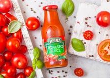 LONDON, UK - SEPTEMBER 13, 2018: Heinz tomato juice with fresh raw tomatoes in box on stone kitchen background. LONDON, UK - SEPTEMBER 13, 2018: Heinz tomato royalty free stock photos