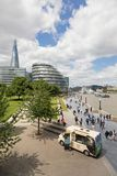 Ice cream van on the Southbank. London, UK - 7th June 2017: Southbank walkway with ice cream van and tourists on the promenade and the City Hall, The Shard and Stock Photo