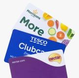 London UK - 14th Maj 2019 - Sainsburys nektarkort, Tesco clubcard och Morrisons mer kort som isoleras på en vit bakgrund royaltyfria bilder