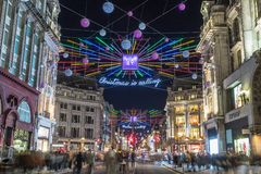 LONDON, UK - 11TH NOVEMBER 2018: Views along Oxford Street with colourful Christmas decorations and lights. Lots of people can be stock photography