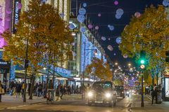 LONDON, UK - 11TH NOVEMBER 2018: Views along Oxford Street with colourful Christmas decorations and lights. Lots of people and a stock photos