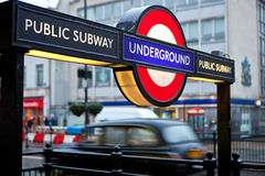 London Underground. Iconic London underground sign and black taxi cab in the rain Royalty Free Stock Photos