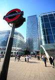 London Underground, Canary Wharf. Wide angle of London Underground sign in front of Canary Wharf with business people and tall office buildings in background Stock Photo