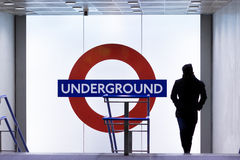 London Underground entrance. LONDON, UK - JANUARY 28, 2016: Silhouetted man exits Kings Cross Underground station at night Royalty Free Stock Photography
