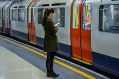 London Underground - girl waiting for train. A picture of a young girl listening to music on her mobile devise about to board a train Royalty Free Stock Image