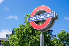 London Underground Roundel. London underground sign pictured against trees and a blue sky Stock Images