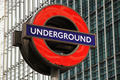 London Underground Sign. The iconic London Underground (The Tube) sign. Located at the financial district of Canary Wharf, with a modern glass building in the Stock Photo
