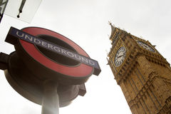 London underground sign and Big Ben. Against white clouds Royalty Free Stock Images