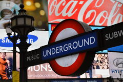 London underground sign Piccadilly Circus neon. London underground sign with Piccadilly Circus neon advertisement in the background Stock Photos