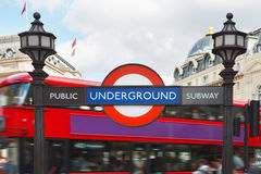London underground sign with street lamps and red bus background Stock Image