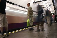 London Underground station platform. London Underground platform, train arriving in motion blur, long exposure. Passengers waiting to embark Royalty Free Stock Photo