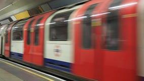 London Underground subway train accelerating at platform station, with motion blur. LONDON, UK - CIRCA SEPTEMBER 2019: London Underground (aka Tube) subway train stock footage