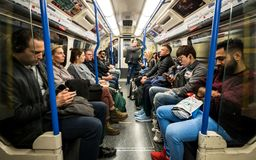 London Underground tube train passengers. LONDON, UK - 5 OCTOBER 2017: An interior view of a busy Piccadilly Line London tube train filled with commuters and Stock Images