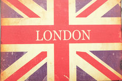 London, Union Jack. A London and Union Jack sign on old woven fabric with stains and scratches Royalty Free Stock Photography