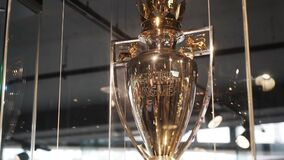 London, United Kindom - February 2, 2020: Close-up of beautiful golden Premier League Trophy standing behind the glass