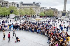 Tourists enjoy the performance show in Trafalgar Square in London, UK. royalty free stock photography