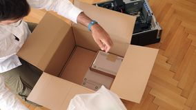 Man unpacking computer parts for upgrade of the Brocken computer dell parts. LONDON, UNITED KINGDOM - CIRCA 2017: Computer geek unboxing unpacking cardboard box stock video footage