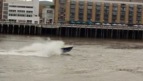 LONDON, UNITED KINGDOM - DECEMBER 10, 2018: Police boat, yacht chasing a criminal, going fast through Themes river, water splashin