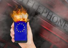 LONDON , United Kingdom : 2019 - Editorial Composite on Brexit. Hand holding mobile phone with European Union flag burning in fire stock photo