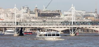 London, United Kingdom - Februari 21, 2019: A City cruises touristic boat navigating by Thames river with a lot of tourists on it. In London, UK royalty free stock photo