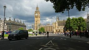 Parliament Square Garden and Big Ben, London, United Kingdom. London, United Kingdom - July 31, 2017: people and city transport near Parliament Square Garden and stock video