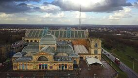 4K aerial view of Alexandra Palace with iconic red double-decker bus stock video