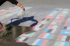 London, UNITED KINGDOM, 09.04.2016. A man cleaning states flags made of chalk, symbolizing nation states crisis Royalty Free Stock Photo