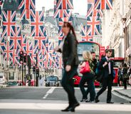 Union Jack Flags on Regent Street. LONDON, UNITED KINGDOM - MAY 18, 2018: Defocused Woman silhouette under Union Jack Flags on Regent Street a day before Royal royalty free stock photography