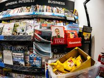 Man shopping for new newspaper in London Press Kiosk. LONDON, UNITED KINGDOM - MAY 20, 2018: Shelves of breaking fresh press in London Press kiosk with various Royalty Free Stock Photos