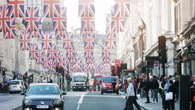 Regent Street sunny atmosphere with Union Jack flags. London, United Kingdom - May 18, 2018: Sunlight over Pedestrians near bus station Volkswagen car under stock video footage
