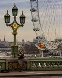 London, United Kingdom - Monday, ‎February ‎6, ‎2017. A bagpiper plays for tips on London`s Westminster bridge. The London Eye can be seen stock photo