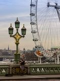 London, United Kingdom - Monday, ‎February ‎6, ‎2017. A bagpiper plays for tips on London`s Westminster bridge. The London Eye can be seen royalty free stock photo