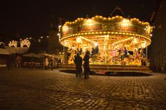 London, United Kingdom - November 25th, 2006: People walking around and watching carousel illuminated in evening at Covent Garden. Which is popular tourist spot royalty free stock photo