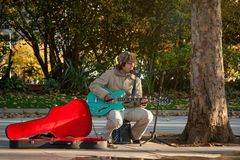 London, United Kingdom - November 18th, 2006: Unknown busker plays guitar and signs at Thames riverside. Street performers are pe. Rforming often in this area stock photo